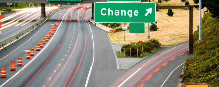 "View of a freeway from an overpass at dusk; the word ""Change"" added in place of an exit name."
